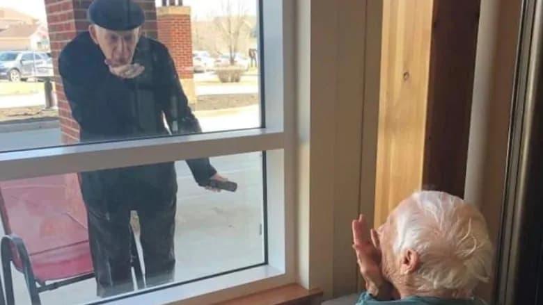 زوج عاشق پس از ۷۰ سال زندگی مشترک، تنها از پشت پنجره برای هم بوسه میفرستند